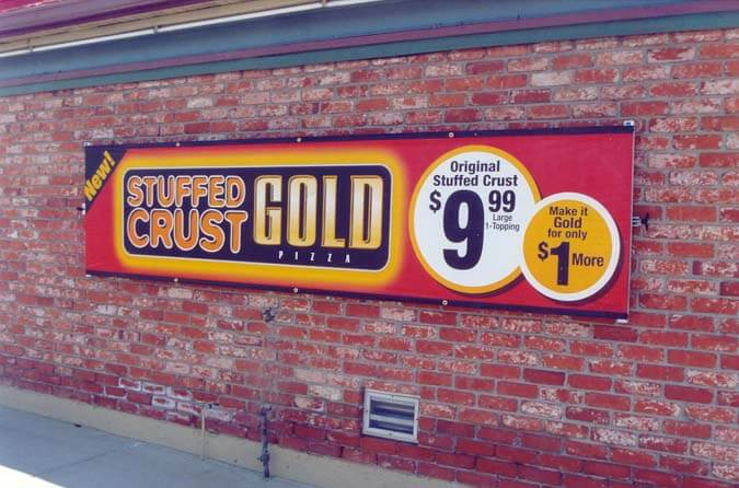 Mounted outdoor banner on brick wall for stuffed crust gold pizza