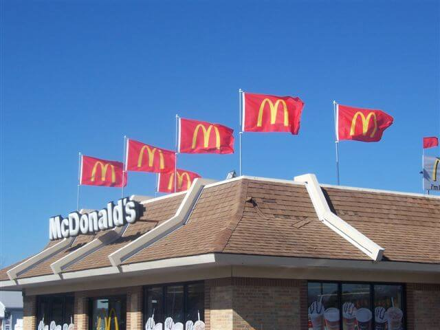 A rooftop display on McDonald's with flags using their logo