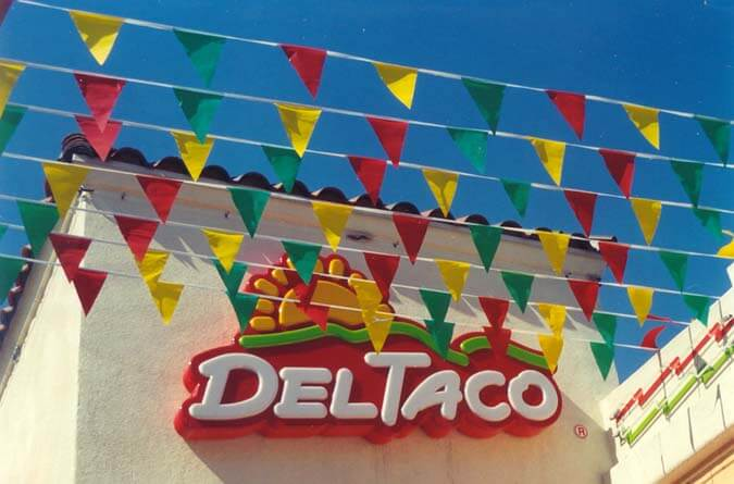 Blade flags on pennant strings in front of Del Taco